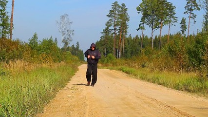 Overweight man running along the forest path