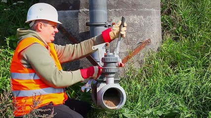 Worker with adjustable wrench at outdoor near pipe