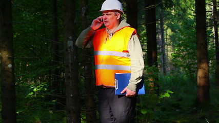 Lumberjack with folder and cell phone in forest