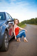 Девушка сидит на дороге летом у автомобиля