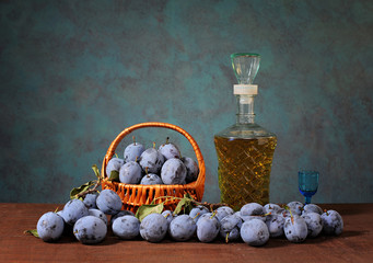 Plums in a wicker basket and plum brandy