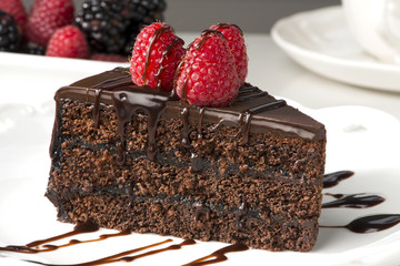 Slice of sachertorte with  berries and chocolate sauce