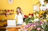 Flower shop owner po...