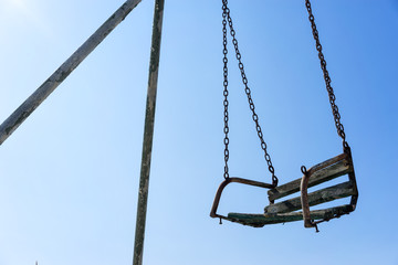 Old rusty swing against blue sky