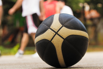 Basketball ball detail with de-focused players in background.
