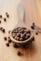 Aromatic whole allspice grains on the old wooden spoon