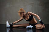 Fototapety Fit woman stretching her leg over dark background