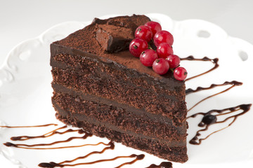 Chocolate layer cake with red currants in white plate