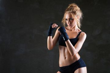 Sexy boxer woman making kick with boxing bandage