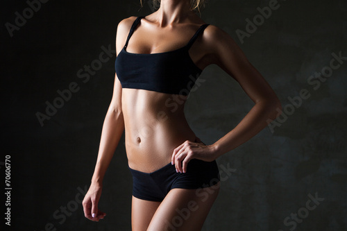 Slim woman's body  over dark grey background - 70606770