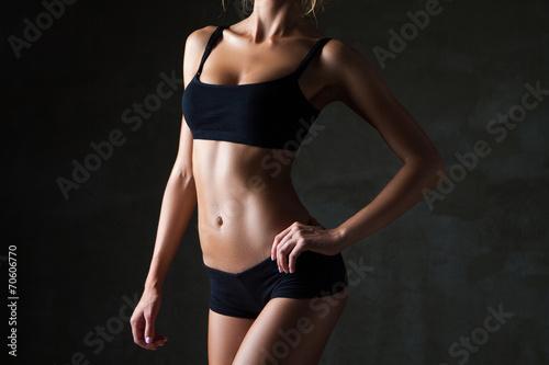 Leinwanddruck Bild Slim woman's body  over dark grey background