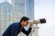 Asian business man with binoculars looking at city
