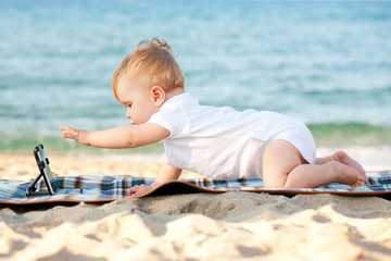 baby with tablet pc on the beach.