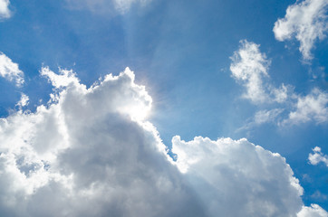 Sun behind cloud and blue sky