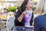 Young cheerful woman laughing while chatting with friend