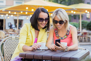 Two cheerful women having friendly chat in cafe
