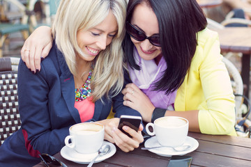 Two female friends viewing photos on mobile phone