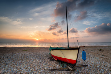 Sailing boat under a beautiful sunrise on a shingle beach