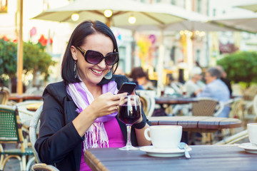 Attractive young woman using mobile phone while sitting in cafe