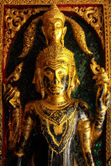 High contrast image of golden buddha sculptures on the temple en