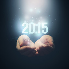 Open hands holding number 2015. Happy New Year.