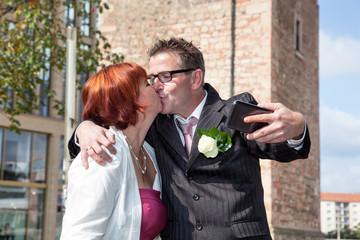 Bride and groom makes selfie before monument