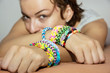 Young caucasian woman with colorful rubber bracelets on her hand