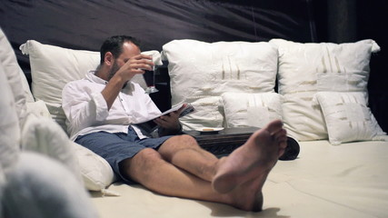 Young man reading magazine, drinking cocktail on bed at night