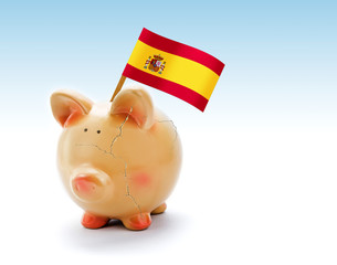 Piggy bank with cracks and national flag of Spain