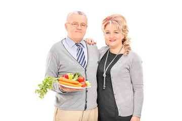 Mature couple holding a plate full of vegetables