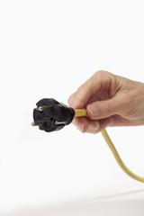 Stromstecker im Hand gehalten auf weißem Hintergrund