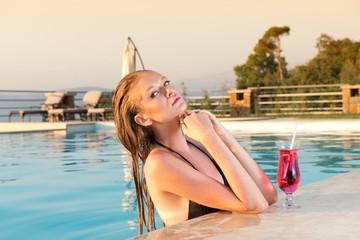 beautiful Blonde girl with fresh juice in luxury pool