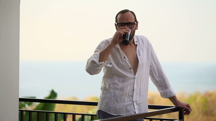 Happy man raising toast with drink on terrace