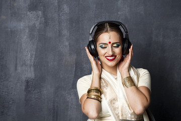Beautiful Indian woman listening to music on headphones