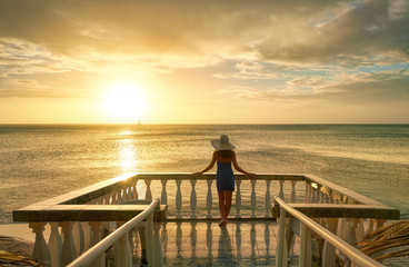 Woman on balcony looking at the beautiful sunset.