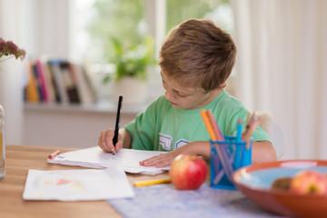 junge sitzt am tisch und malt ein bild