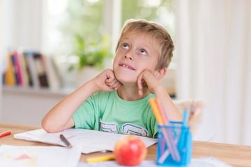 kleiner junge malt ein bild und denkt an nach