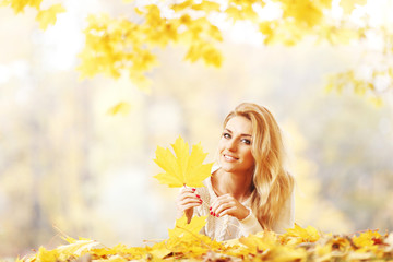 Woman laying on autumn leaves