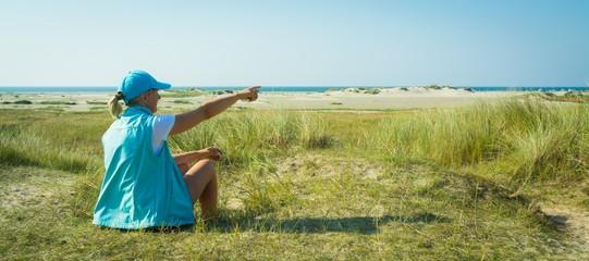 Frau sitzt am Stand der Nordsee