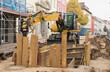 Ein Bagger hinter einer mit Verbauplatten gesicherten Baugrube