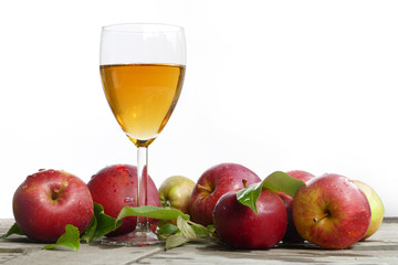 apple juice in a glass and red apples with leaves on old wood, w