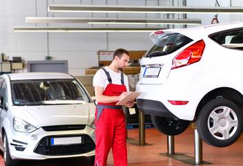 KFZ Mechaniker kontrolliert Auto // succesfull workman
