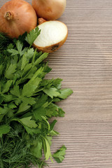 Fresh cooking ingredients with onions and fresh herbs on a woode