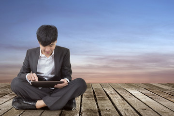 Asian business man using pad and sit on ground