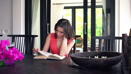 Beautiful woman reading book by dining table at home