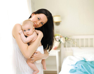Happy mom hugs baby, home in the bedroom