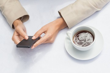 Businesswoman using smartphone with coffee
