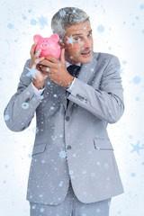 Composite image of curious businessman holding piggy bank