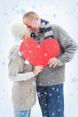 Mature couple in winter clothes holding red heart