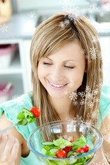 Young woman eating a salad in the kitchen
